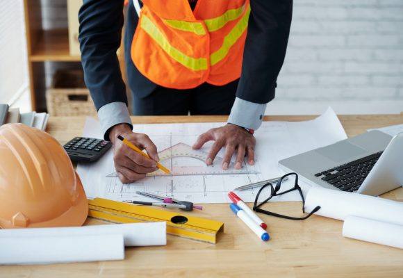 pracownik budowy kreśli na projekcie