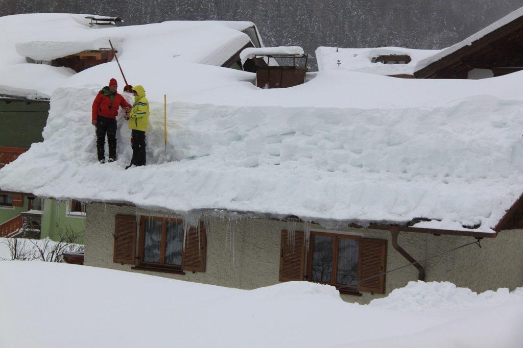 mężczyźni odśnieżający dach